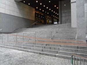 Colour photograph showing the same dangerous public ramp/stair combination near the Main Public Entrance to the European Parliament Building, on Rue Wiertz, in Brussels. During rush hour periods of the working day, this external ramp/stair combination is a very busy public pedestrian route. Click to enlarge. This photograph taken by CJ Walsh. 2010-02-24. For more photographs of this architectural gem, dating from 2000-2001, see SDI's Corporate WebSite.