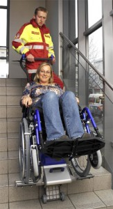 Colour photograph showing a Powered Fire Evacuation Chair Device in operation. This particular device facilitates evacuation, down and up a staircase, using the person's own manual wheelchair. Having completed its task at the bottom (or top !) of a staircase ... the device can be quickly released for use by another person who needs assistance on the staircase. Throughout this process, wheelchair users move independently to a Place of Safety. Click to enlarge.