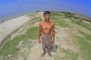 Colour photograph showing Ruhul Khan, who has lost three houses in recent years. His former homes were located to the left of the picture, an area now covered by water.