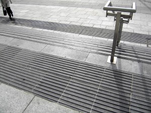 Colour photograph showing details of the steps, handrails and tactile ground surface indicators at the Main Entrance to the New Criminal Courts of Justice Building in Dublin, Ireland. Photograph taken by CJ Walsh. 2011-03-30. Click to enlarge.