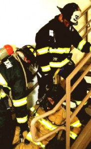 Colour photograph showing an injured, or impaired, firefighter being assisted by two colleagues in an upward staircase removal exercise. For reasons outlined in a previous post (2010-12-13) ... all three firefighters must continue to wear full Personal Protection Equipment (PPE) ... and use Self-Contained Breathing Apparatus (SCBA). Click to enlarge.