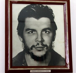 Colour photograph showing a framed head and shoulders of the young Dr. Ernesto 'CHE' Guevara de la Serna Lynch in a small museum in the central square of Yara (Plaza Grito de Yara), Cuba. Centuries earlier, nearby, the Indian hero Hatuey was burned at the stake. Photograph by CJ Walsh. 2007-04-10. Click to enlarge.