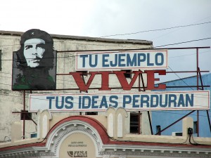 "Colour photograph showing a hoarding on the roof of a building in Cienfuegos, Cuba ... which comprises an image of CHE, with the accompanying text ""Tu Ejemplo Vive - Tus Ideas Perduran"". Photograph by CJ Walsh. 2007-04-13. Click to enlarge."