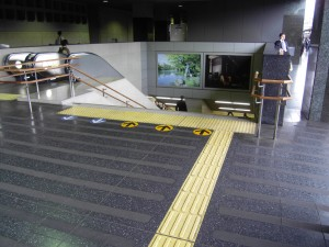 Colour photograph showing a main circulation route at a Railway Station in Kyoto, Japan ... with combined staircase and elevators. Notice, in particular, the dual height staircase handrails, for adults and children ... the strong contrast of the floor tactile information (a 'directional' indicator leading to a 'hazard' indicator, at the top of the staircase) compared to the rest of the floor, with its broad non-slip strips ... and, finally, arrows used to control staircase circulation flows at peak periods (down to the right, up on the left). Photograph taken by CJ Walsh. 2010-04-27. Click to enlarge.