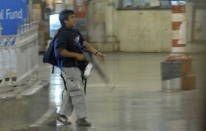 Colour photograph showing an armed assailant during the November 2008 'Hive-Attack' on Mumbai ... an extraordinarily violent, co-ordinated assault on the largest (and wealthiest) city in India, which involved the strategic targeting of built environment Places of Public Resort, Iconic Buildings, High-Rise Buildings, Buildings having a Critical Function, Transport Infrastructure and Service Utilities ... with the aim of causing widespread terror among the general population, including tourists, and disruption to the city's important economic environment. Click to enlarge.