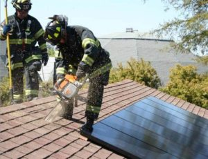 Colour photograph showing two firefighters on a roof, one with cutting equipment. Solar Photovoltaic Roof Panels restrict firefighter access to building interior roof spaces.